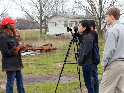 Three students filming an interview outside