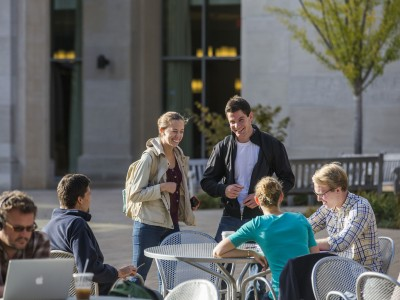 Smiling students chat outside around tables