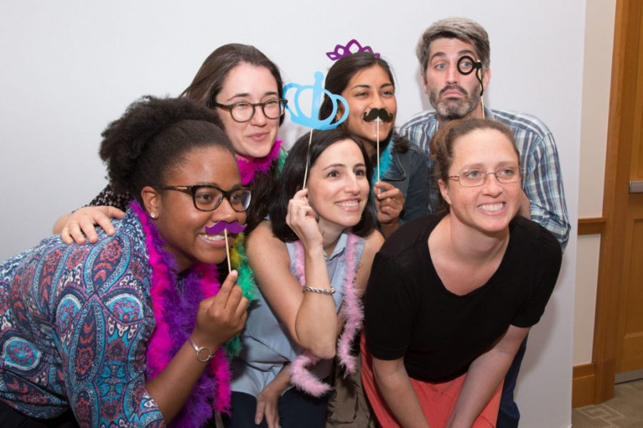 A group of staff members pose in the photo booth