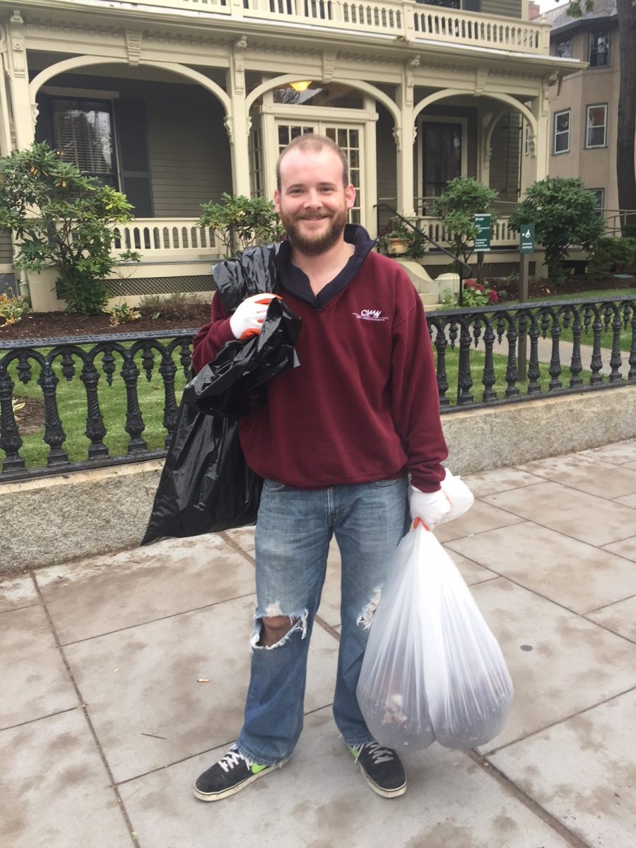 One participant hauls two trash bags after cleaning out tree wells