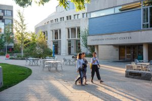 Three students walk outside of the Caspersen Student Center