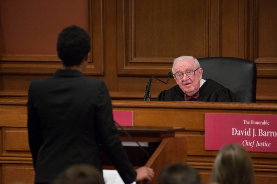 Retired Justice Stevens speaks to a student from the bench
