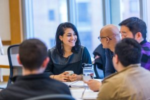Several students talk and smile at a table