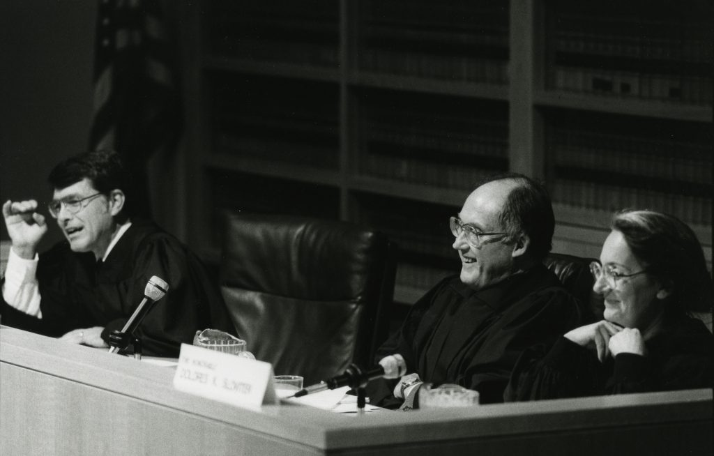 Three judges smiling at the bench