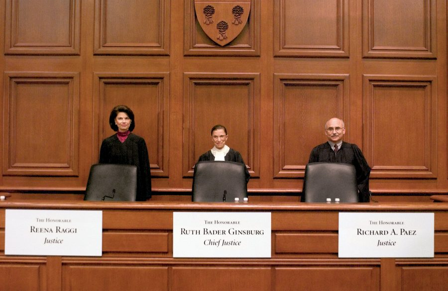 Three judges stand behind their chairs in a courtroom