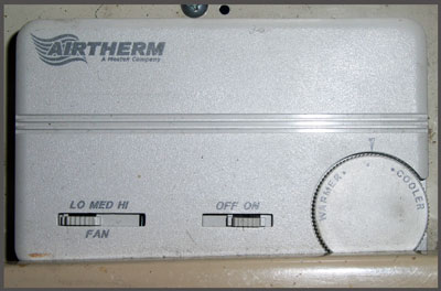 Thermostat with sliders on left and middle, and a dial on the right.