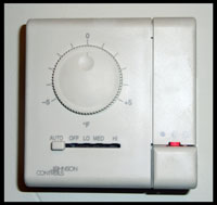 Thermostat with adjustment knob, settings switch, and red light indicator.