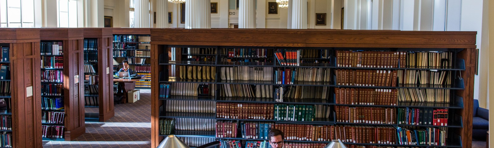 Students sit at a table and study in front of shelves of books in the Harvard Law Library.