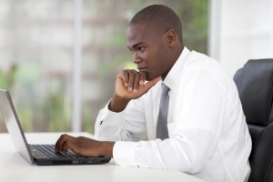 Man at desk pensively reading from laptop