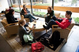 A group of students in conversation at a round table, with coffee