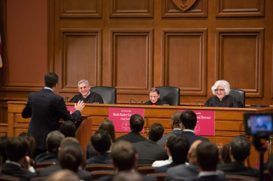 Three judges on the bench respond to an oralist speaking at the podium