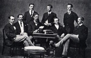 Men in 1800's clothing sit posed for the camera