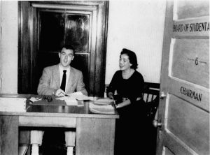 A man and woman sit at a desk in the board of student advisors office