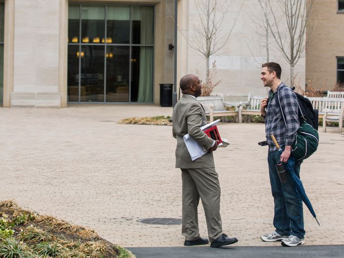 Professor and student talk outside an HLS building