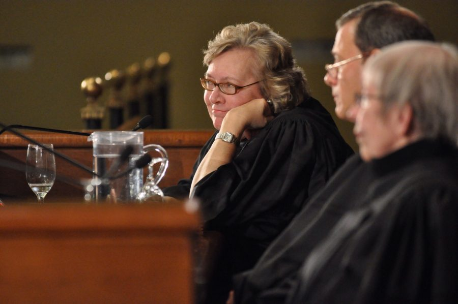 Judge sits with smiling face resting on her hand