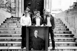 Six participants of the Ames Moot Court stand on the library steps behind a portrait of a judge