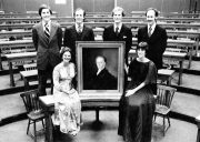 Participants at the Ames Moot Court Competition pose with a portrait of a judge