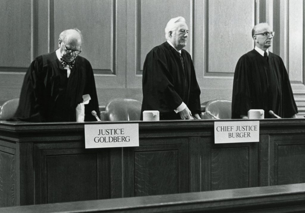 Three judges stand at the bench at the Ames Competition