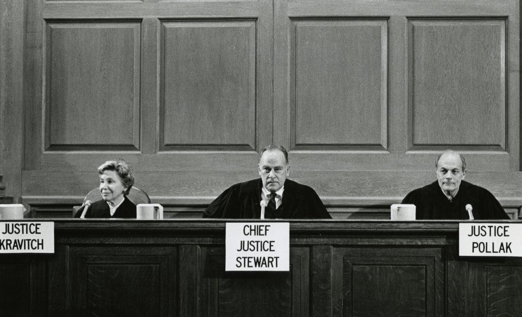 Three judges sit behind the bench at Ames Moot Court Competition
