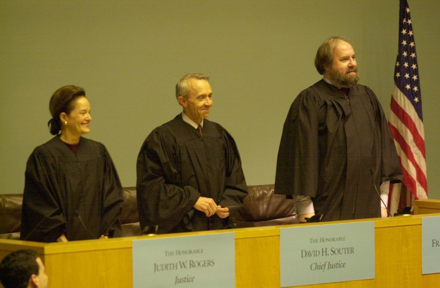 Three judges stand at the bench