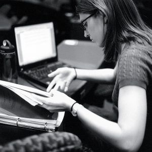 Woman looks through papers while sitting at a computer