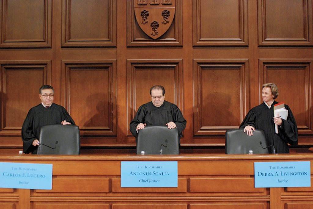 Three judges stand behind chairs on the bench
