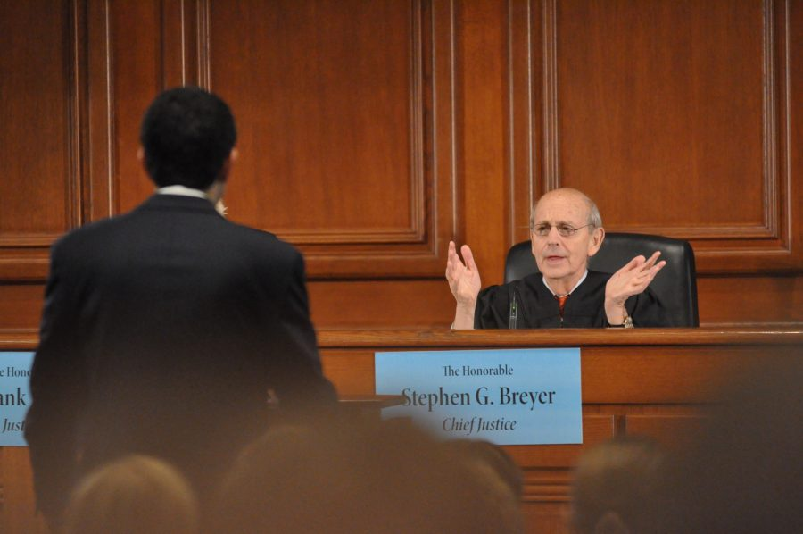 A judge speaks to an oralist at the podium during Ames moot court