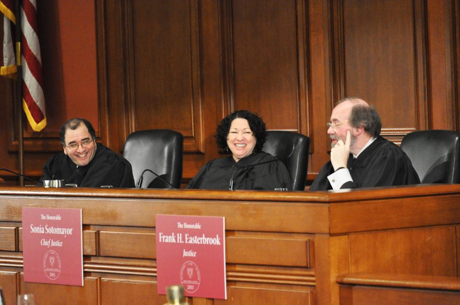 Three judges smile while sitting at the bench