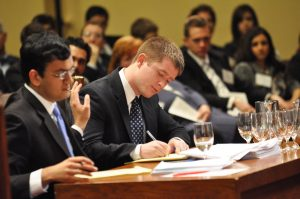 Two Ames moot court competitors write notes during the Ames competition