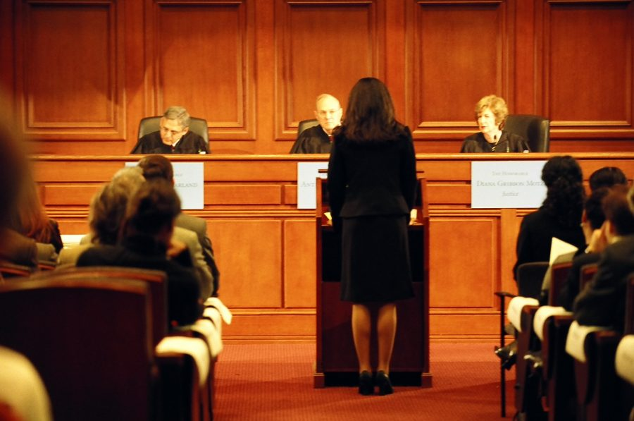 Oralist stands at podium and speaks to three judges