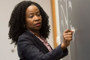 Professor, Ruth Okediji writes on a chalkboard