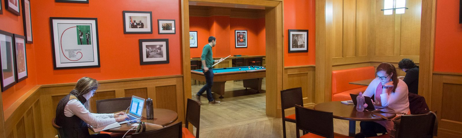Students study in the pub while another plays pool