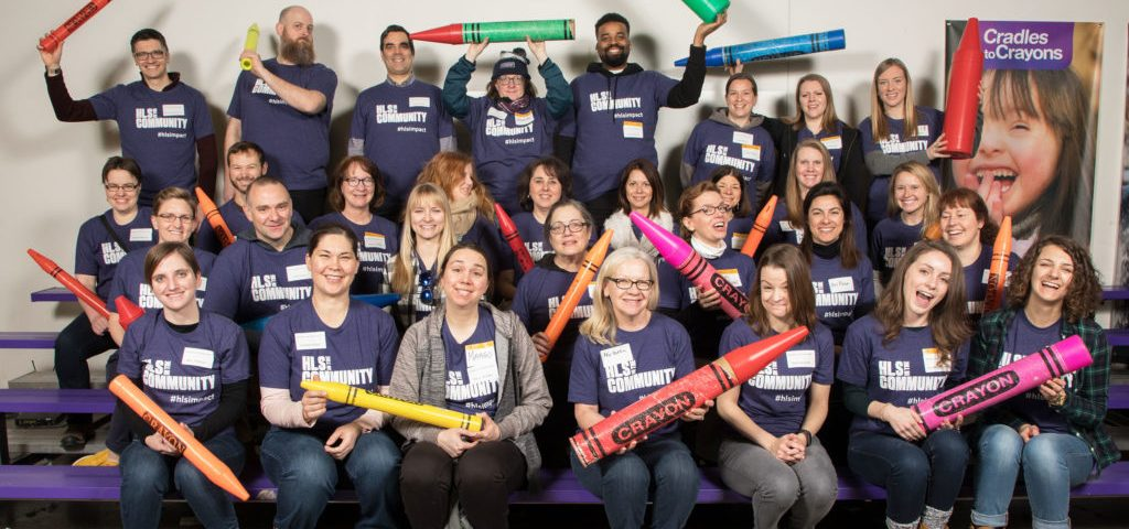 A large group of staff pose with large crayons