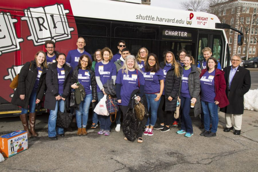 A group of staff in matching purple t-shirts stand next to a shuttle bus