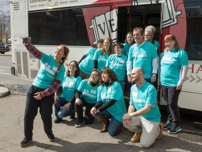 Several staff in matching blue t-shirts pose for a selfie beside a shuttle bus