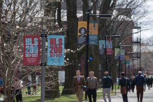 People walk across campus under HLS 200 banners