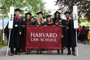"""Graduates hold a """"Harvard Law School"""" banner and """"Law"""" signs"""