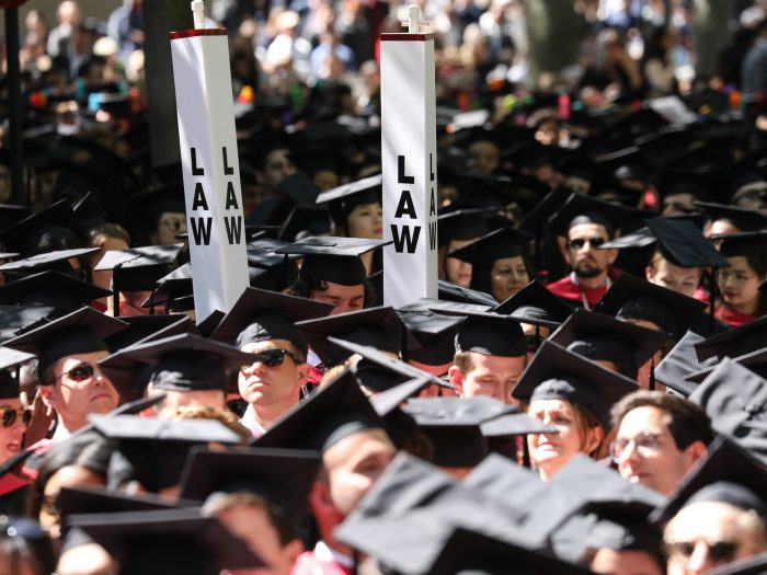 """""""Law"""" signs above graduates' heads"""