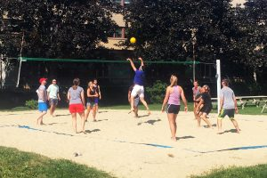 People playing volleyball on a sandy court