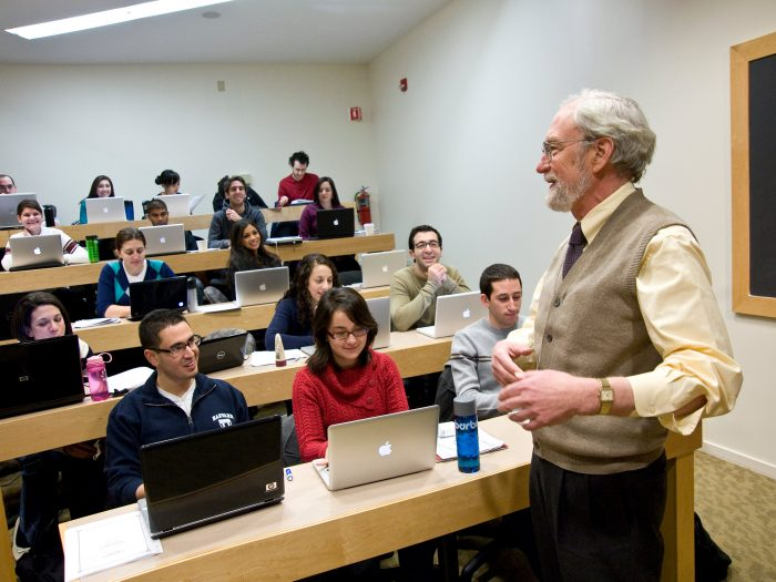 Professor stands in front of classroom and speaks to students