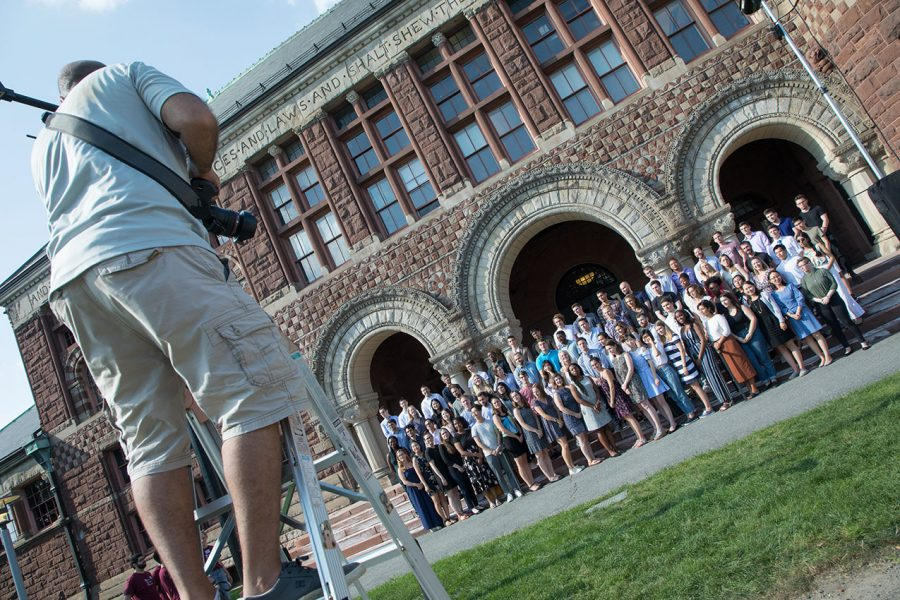 Photographer on a ladder takes a picture of a large group of students