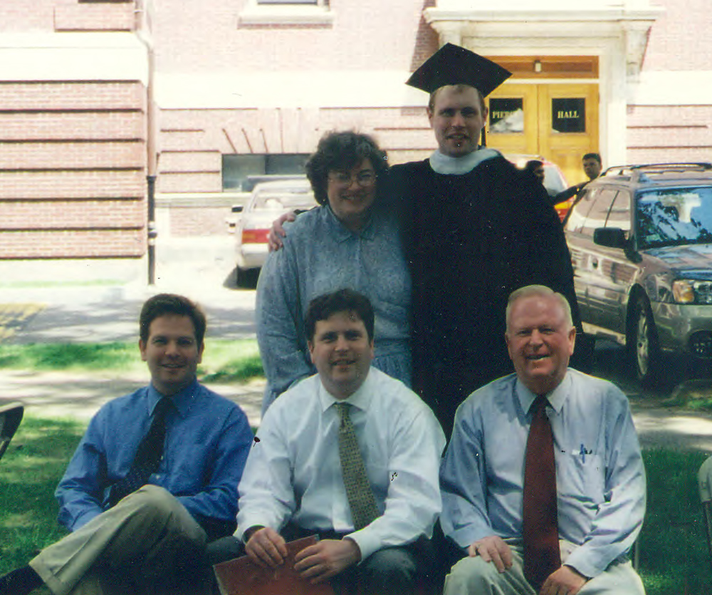 Cam MacDougall '01 in his HLS graduation robe standing with his family including his parents and two brothers.