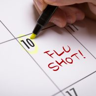 Person adding 'flu shot!' to a calendar