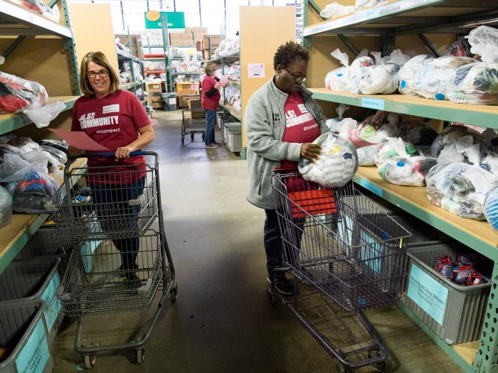 Two volunteers take items from factory shelves to put in shopping baskets