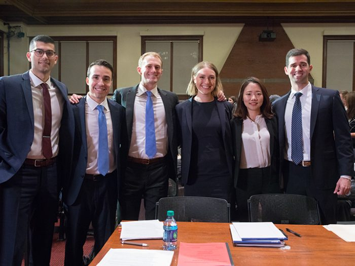 Six participants in the Ames Moot Court final round stand together with arms linked