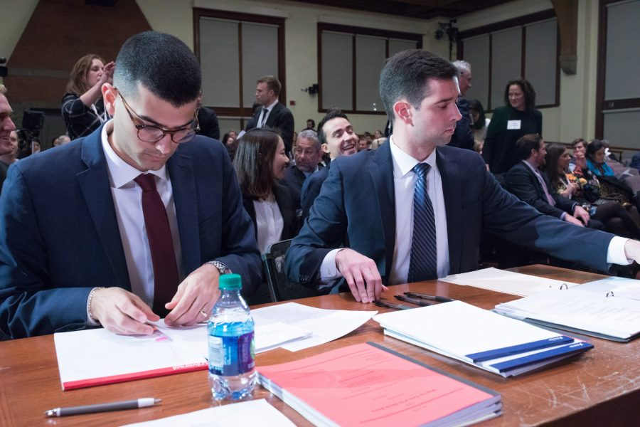 Two Ames Moot Court participants look at papers on a desk in front of a seated crowd