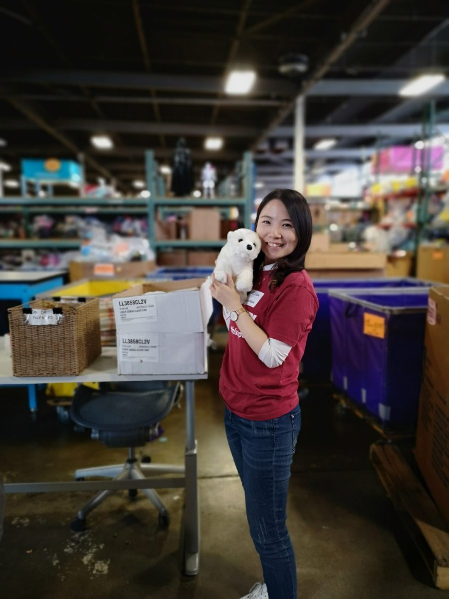 A staff member holds a stuffed animal in the Cradles to Crayons warehouse