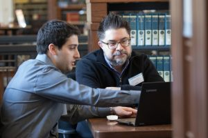 A student and professor Christopher Bavitz look at a laptop screen together