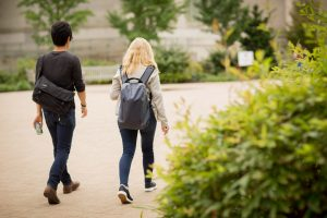 Two students walk across campus