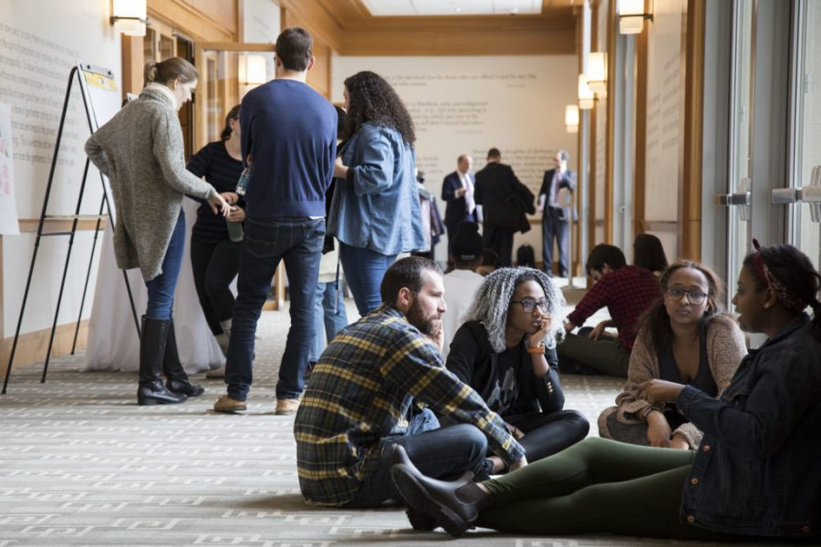 Students gather in groups, standing and sitting on the ground